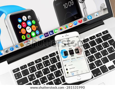 Moscow, Russia - May 26, 2015: Apple watch on iPhone 6 and Macbook display. Apple Watch is a smartwatch developed by Apple Inc.