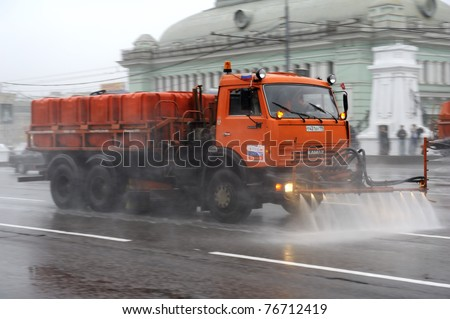 MOSCOW, RUSSIA - MAY 07: Big orange street cleansing machine washes the asphalt road  May 07, 2011 in Moscow, Russia.