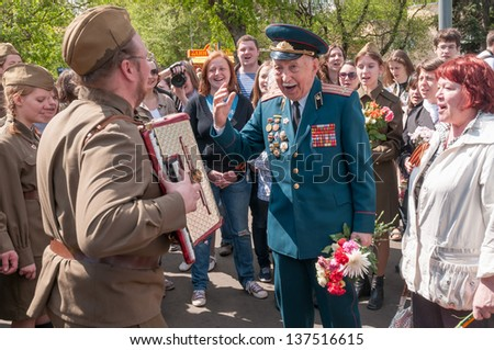 MOSCOW/RUSSIA - MAY 9: Veteran of war and accordion player in WWII uniform surrounded with other people during festivities devoted to anniversary of Victory Day on May 9, 2011 in Moscow.