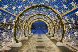 MOSCOW, RUSSIA - New Year and Christmas light installation in form of a tunnel with stars and LED lights in the park Khodynskoye Pole in blue hour on the last evening of winter holidays in Russia.