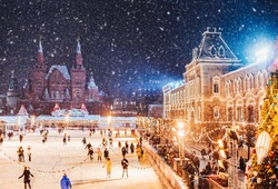 Moscow, Russia New Year.  Saint Basil's Cathedral on the background.  Christmas holidays, snowy winter night landscape. Christmas fair on Festively decorated Red Square in snow. Christmas Market.