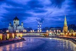 MOSCOW, RUSSIA - Night winterscape in the blue hour with the view from Bolshoy Moskvoretsky Bridge on the icy river Moskva (Moscow), Cathedral of Christ the Savior, and the tower of the Kremlin