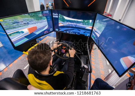 MOSCOW, RUSSIA - OCTOBER 27 2018. Young man plays on a computer racing simulator with big screens #1218681763