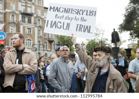 MOSCOW , RUSSIA - SEPT 15. Tens of thousands oppositionist  marched through Moscow in protest against President Putin . Man hold poster in support Magnitsky list. on September 15, 2012, Moscow #112995784