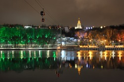 MOSCOW, RUSSIA - The aerial cable line over the river Moskva (Moscow) leading to the festively illuminated with colorful spotlights trees of Sparrow Hills (Vorobyovy Gory) park on a winter evening.
