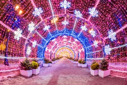 Moscow. Russia. Tunnel of Christmas garlands. A long tunnel of glowing garlands. New Year's illumination on the streets of Moscow. Snow. Walks in the winter capital. Tour of Russian cities.