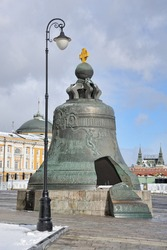 MOSCOW, RUSSIA - View of the 6 meter tall Tsar Bell (Tsar-kolokol) with a broken piece framed by a street lamp on display on the grounds of the Moscow Kremlin.