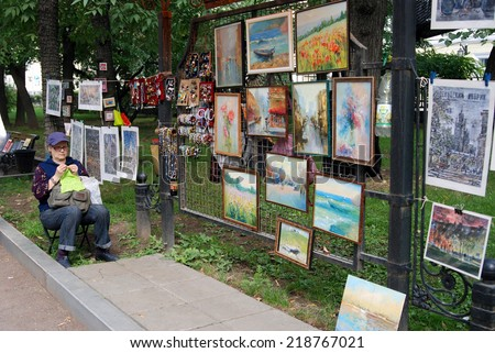 MOSCOW - SEPTEMBER 06, 2014: A seller of paintings on Gogol boulevard in Moscow. Moscow City Day celebration in Moscow city center.