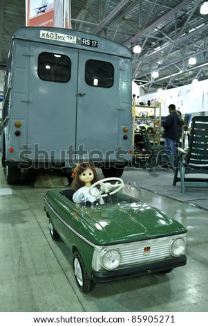 MOSCOW - SEPTEMBER 16: Doll sits in old toy car AZLK Moskvich (car in focus) at the international exhibition of the technical antiques on September 16, 2011 in Moscow, Russia
