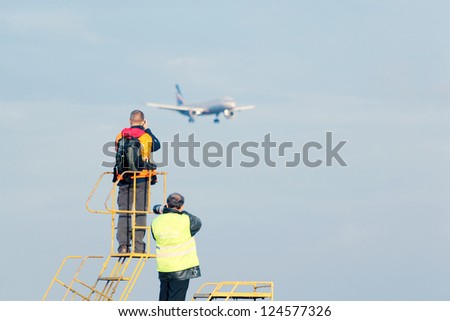 MOSCOW - SEPTEMBER 22: Men shoot at traditional spotting for professional and amateur aviation photographers in Sheremetyevo on September 22, 2011 in Moscow, Russia.
