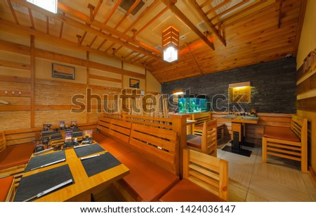 "MOSCOW - SEPTEMBER 2014: The interior of the popular Japanese chain of restaurants ""YAKITORIYA"" in Moscow. The hall of the Japanese-style restaurant with wooden furniture #1424036147"