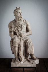 Moses statue on wooden floor and white background