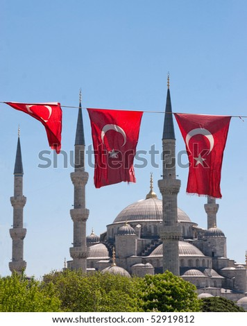 Mosque behind turkish flags in blue sky