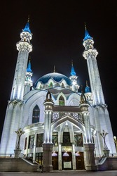 Mosque of Kul Sharif and its minarets directing to the black sky on night. Building is illuminated by artificial lights. Inscription above doorway is name of mosque in Tatar. Shot in Kazan, Russia