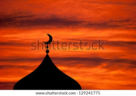 Mosque silhouette against vivid red sunset sky