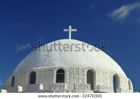 Mosque style dome topped chapel is framed by vivid blue skies.  Small cross tops roof.