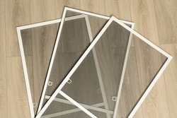 Mosquito nets for windows on a wooden floor background . Protection from fly and insects