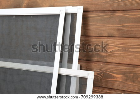 Mosquito window screens on wooden background #709299388