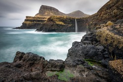 Moss Foreground with Volcanic Rock and Background of Cliff and Waterfall. Gasadalur, Faroe islands, Denmark,Europe