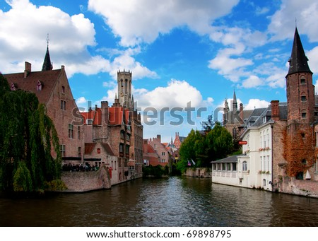 Most common view of medieval Bruges against blue cloudy skies.