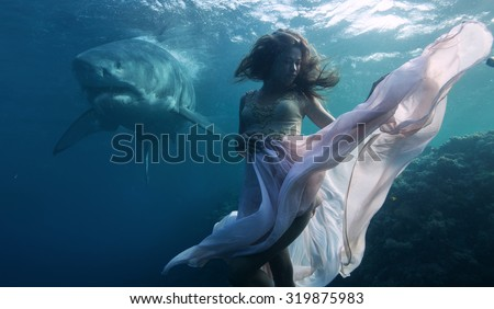 Stock Photo Most dangerous predator in The Ocean Great White Shark peaceful floating behind model posing underwater in fashion dress. Beautiful Model in deep sea in weightless condition hovering over coral reef.