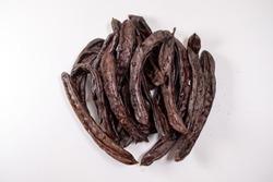 most known as  Ceratonia siliqua L.  or Keciboynuzu or carob or kharnub isolated on white background top view photo .