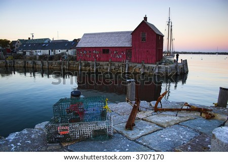 Most photographed famous fishing shack in Bearskin Neck Wharf in New England on the background with antique anchors on the foreground.
