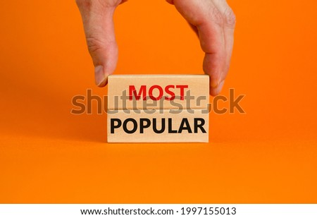 Most popular symbol. Concept words Most popular on wooden blocks on a beautiful orange background. Businessman hand. Copy space. Business and Most popular concept. Stock fotó ©