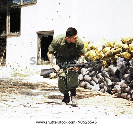 MOSTAR, BOSNIA - MAY 24: A Bosnian-Croatian soldier runs for cover during a pitched battle on Monday, May 24, 1993 in Mostar, Bosnia.