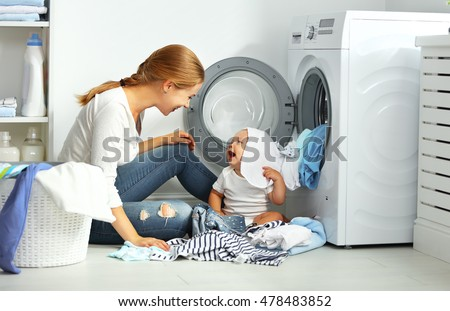 mother a housewife with a baby engaged in laundry fold clothes into the washing machine #478483852