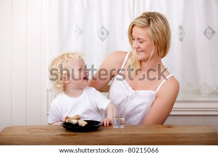 Mother a son laughing while eating lunch at a table