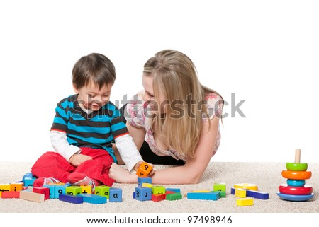 Mother and a little son are playing on the carpet with blocks; isolated on the white background