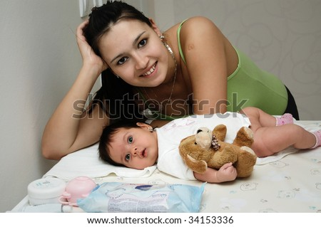 mother and a newborn baby girl after changing diaper looking happy
