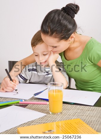 mother and a 5-year old son painting on paper - stock photo