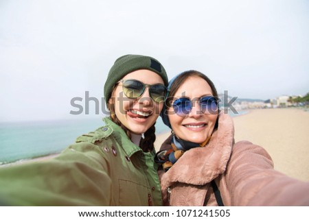 Mother and adult daughter are doing selfie on the beach in Barcelona, going crazy and showing tongue.Happy and positive emotions.Hipster family.Parents and teenagers.Tourist Vacation self-portrait