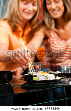 mother and adult daughter eating sushi at home focus is. Black Bedroom Furniture Sets. Home Design Ideas