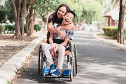 Mother and Asian Disabled child on wheelchair is playing, learning and exercise in the outdoor city park like other people with family,Life in the education age,Happy disability kid concept.