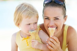 Mother and baby biting ice cream