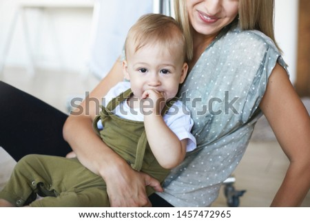 Mother and baby bonding at home. Indoor image of unrecognizable young woman hugging tight her cute eight month old son. Happy mom and adorable infant child spending nice time together indoors