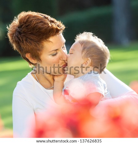 Mother and baby boy in park portrait