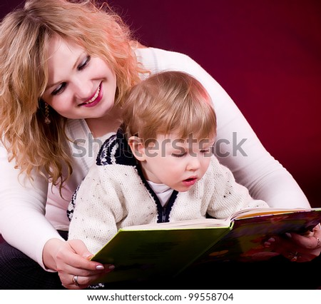 Mother and baby boy reading book and smiling  on red background