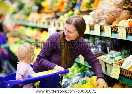 Mother and baby daughter in supermarket buying fruits