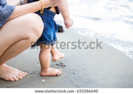 mother and baby feet at the sea ...