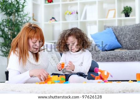mother and baby  girl playing with blocks on living room floor