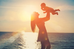 mother and baby having fun at sunset on the beach