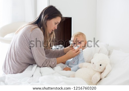 Mother and baby in pajamas, early in the morning, mom taking care of her sick toddler boy. Baby in bed with fever and running nose