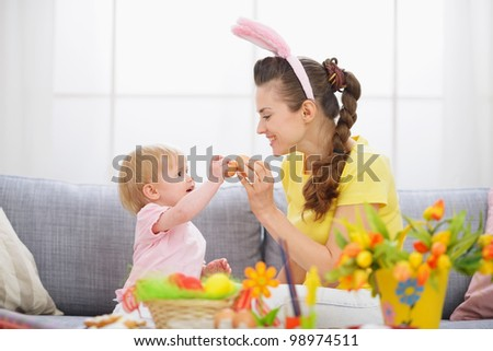 Mother and baby knocking Easter eggs