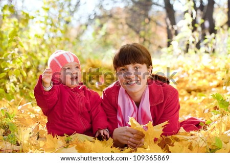 Mother and   baby laying on maple leaves in autumn park