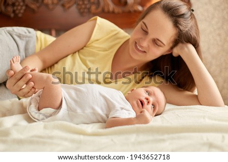 Mother and baby lying on bed on white blanket, smiling mommy wearing yellow t shirt enjoying to spend time with her newborn kid, infant looking away to study outward things. Stock photo ©