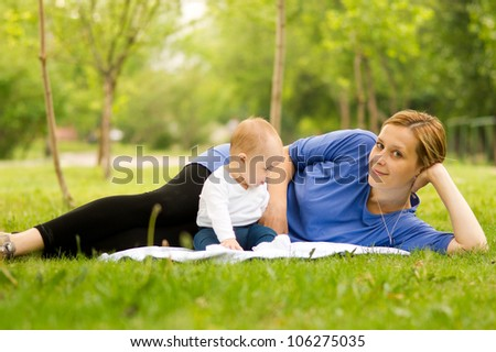Mother and baby lying on the grass